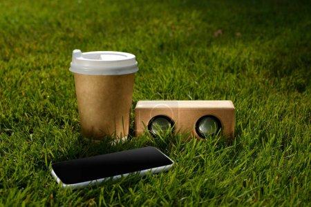 Nahaufnahme von Coffee to go, Smartphone und Lautsprecher auf grünem Gras