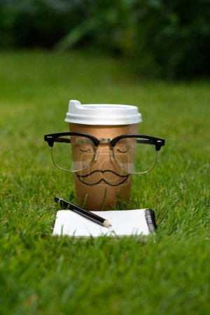 close up view of disposable cup with mustache sign, eyeglasses and notebook with pencil on green grass