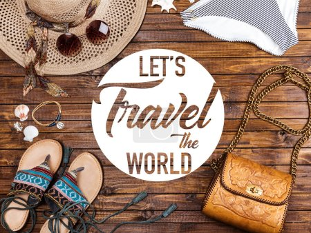 "Top view of swimming pants, straw hat, sunglasses, sandals and bag on wooden table with ""lets travel the world"" lettering"