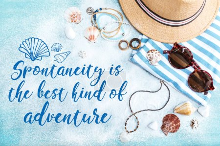 "Top view of straw hat, sunglasses and striped clothes on blue tabletop with white sand. Summer holidays concept with inspiration ""Spontaneity is the best kind of adventure"""