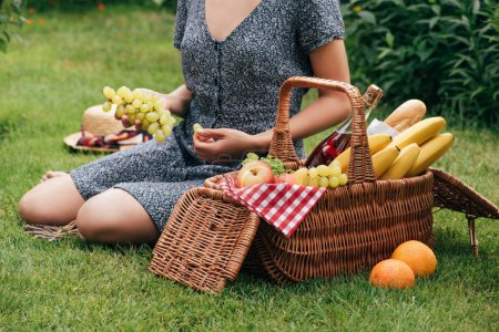 cropped image of woman eating grapes and sitting on green grass at picnic