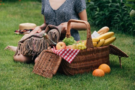 cropped image of woman sitting on green grass at picnic and holding blanket