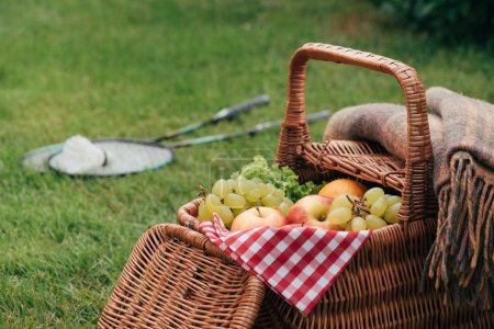 delicious fruits in basket on green grass in park