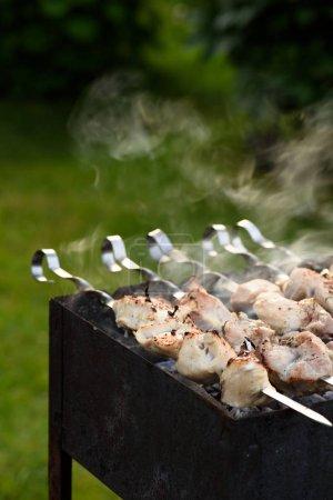 preparation of pork kebab on skewers at barbecue