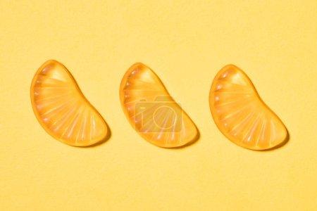top view of gummy orange candies on yellow