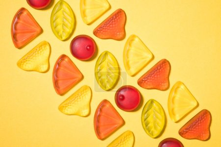 top view of gummy fruits in row on yellow surface