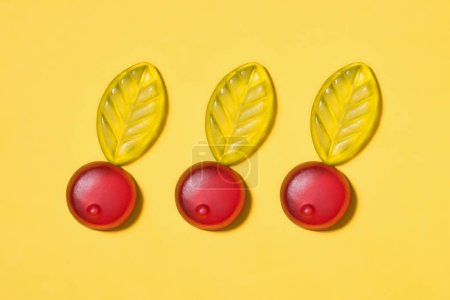 top view of gummy cherries on yellow surface