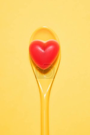 top view of delicious candy in shape of red heart on spoon and on yellow surface