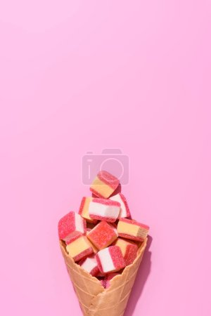 top view of sweet gummy candies in waffle cone on pink