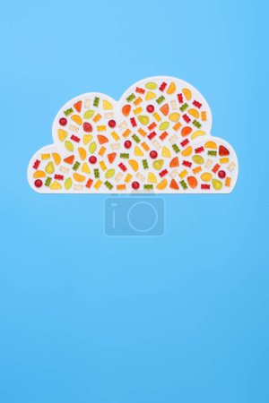 top view of cloud made of gummy candies isolated on blue