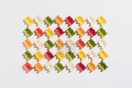 top view of colorful gummy bears pattern on white