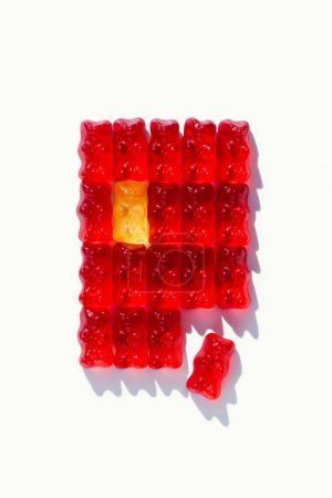 top view of red defragmented rectangle of gummy bears on white