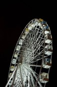 selective focus of illuminated observation wheel at night on black background