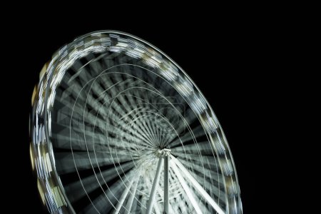 selective focus of defocused observation wheel at night on black background