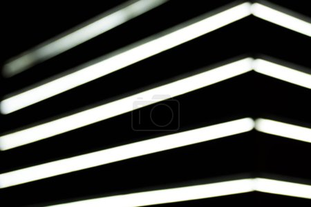 close up view of blurred white lightning lamps on black background