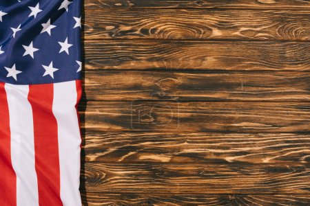 top view of folded american flag on wooden tabletop, americas independence day concept
