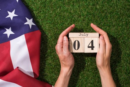 cropped shot of man holding calendar with 4th july date with american flag on green grass, americas independence day concept