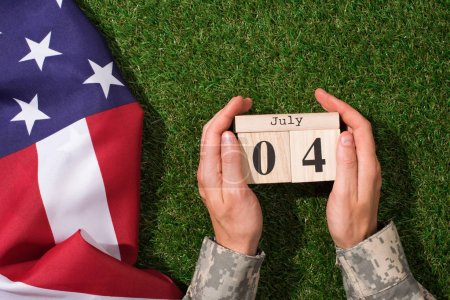 cropped shot of soldier in military uniform holding calendar with 4th july date with american flag on green grass, americas independence day concept