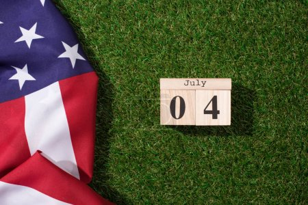 Photo for Top view of american flag and wooden calendar with 4th july date on green lawn, americas independence day concept - Royalty Free Image