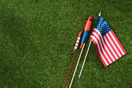 flat lay with american flagpole and fireworks on green grass, americas independence day concept