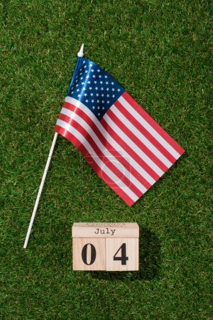 top view of american flagpole and wooden calendar with 4th july date on green grass, americas independence day concept