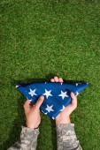 partial view of soldier in military uniform holding folded flag in hands on green grass, 4th july holiday concept