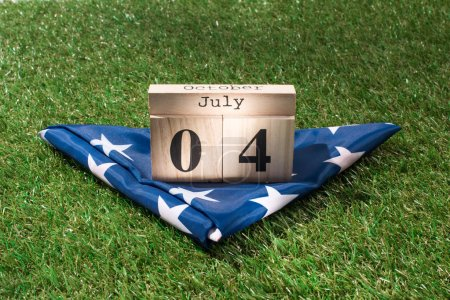 close up view of folded american flag and wooden calendar with 4th july date on green lawn, americas independence day concept