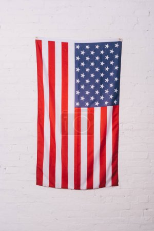 close up view of american flag hanging on white brick wall