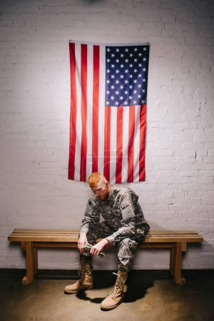 red hair american soldier sitting on wooden bench with flag on white brick wall behind, americas independence day concept