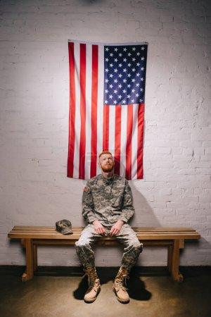Photo pour Soldat américain cheveux roux assis sur un banc en bois avec le drapeau sur le mur de brique blanche derrière, concept de jour de l'indépendance Amériques - image libre de droit