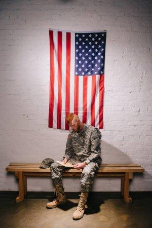 Photo pour Soldat américain cheveux roux avec lettre assis sur un banc en bois avec le drapeau sur le mur de brique blanche derrière, concept de jour de l'indépendance Amériques - image libre de droit