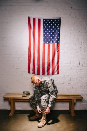 american soldier in military uniform tying shoelaces with flag on white brick wall behind, 4th july holiday concept