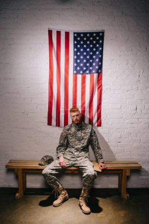 soldier in military uniform with letter sitting on wooden bench with american flag on white brick wall behind, 4th july holiday concept