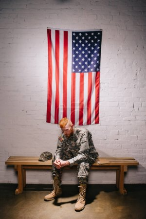 soldier in military uniform sitting on wooden bench with american flag on white brick wall behind, 4th july holiday concept