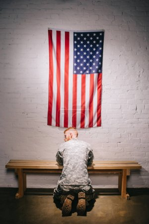 rear view of soldier in military uniform praying with american flag on white brick wall, americas independence day concept