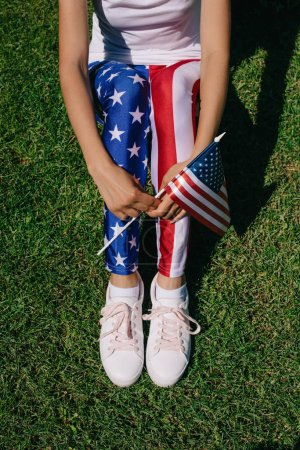 partial view of woman with flagpole in leggins with american flag pattern resting on green lawn, americas independence day holiday concept