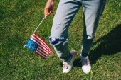 cropped shot of woman in denim with american flagpole in hand standing on green grass, 4th july holiday concept