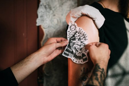 cropped shot of tattoo artist transferring tattoo sketch on shoulder in tattoo salon