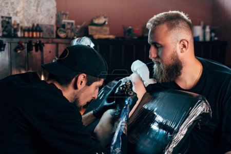 side view of tattoo artist in gloves working on tattoo on shoulder in salon