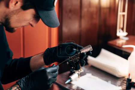 selective focus of tattoo artist in gloves with tattooing machine in salon