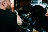 mise au point sélective du tatoueur en blouson avec machine de tatouage travaille sur tatouage épaule au salon