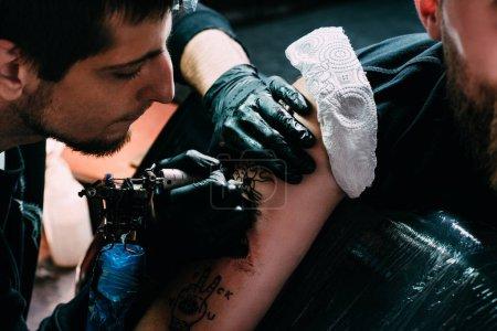 Foto de Recortar el tiro de tatuador centrado en guantes de trabajo de tatuaje en el hombro en el salón de - Imagen libre de derechos