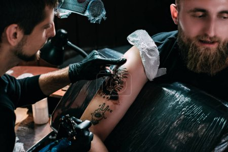 selective focus of tattoo artist in gloves working on tattoo on shoulder in salon