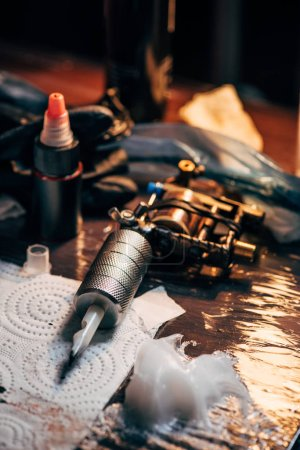close up view of tattoo machine, ink and other equipment for tattooing process