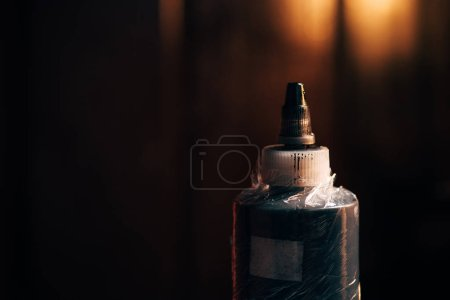 close up view of bottle with tattoo paint with blurred background