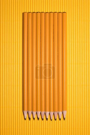 top view of arranged graphite pencils placed in row on yellow