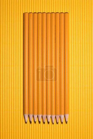 Photo pour Vue de dessus des crayons graphite arrangés mis en ligne sur jaune - image libre de droit