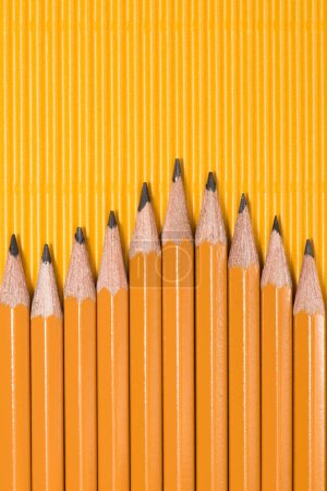 top view of graphite pencils placed in row on yellow
