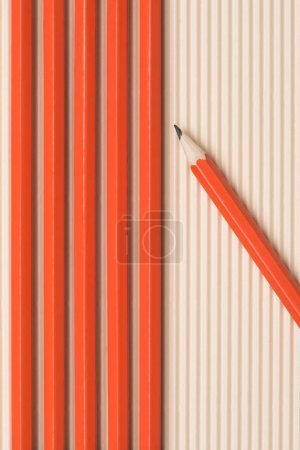 elevated view of graphite pencils placed in row on beige