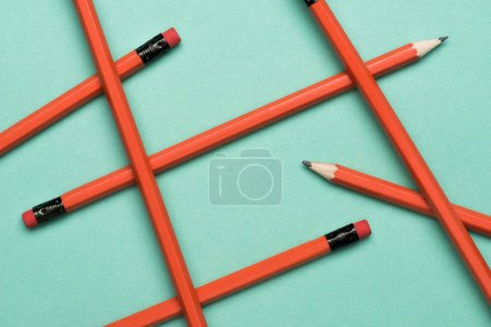 top view of arranged graphite pencils with erasers on green